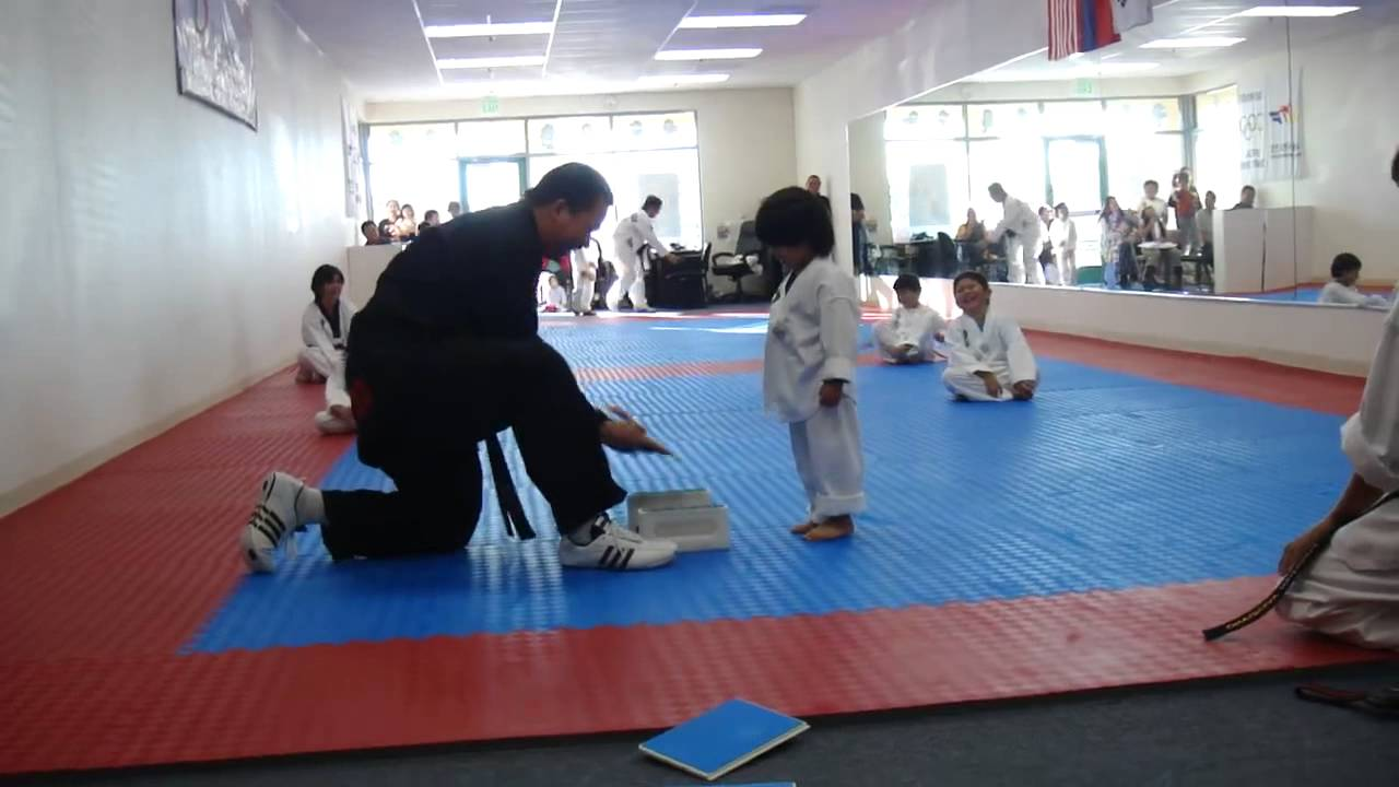 Un enfant essaie de briser une table en cours de taekwondo